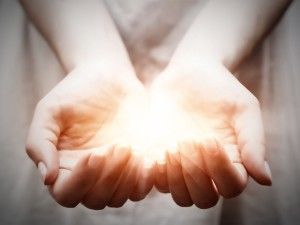 Cupped hands held together and holding a luminous ball of light
