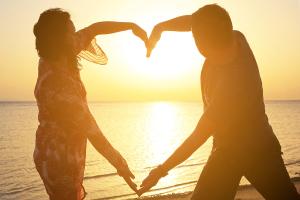 Couple making romantic heart shape at sunrise on the beach