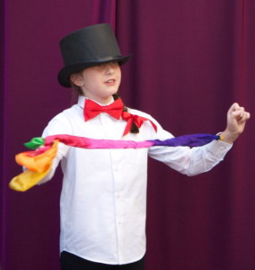 Sweet 8 year old student singing, wearing a top hat, performing a magic trick, pulling a colorful scarf out of her sleeve