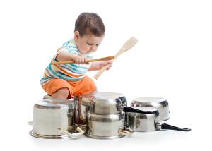 little kid boy drumming on kitchen pots