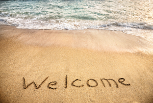 The word welcome written in sand on beach, with waves in the background
