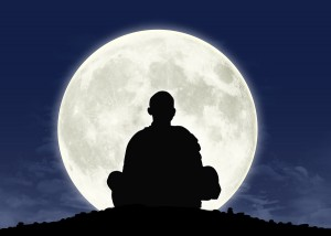 Silhouette of person meditating in front of a full moon