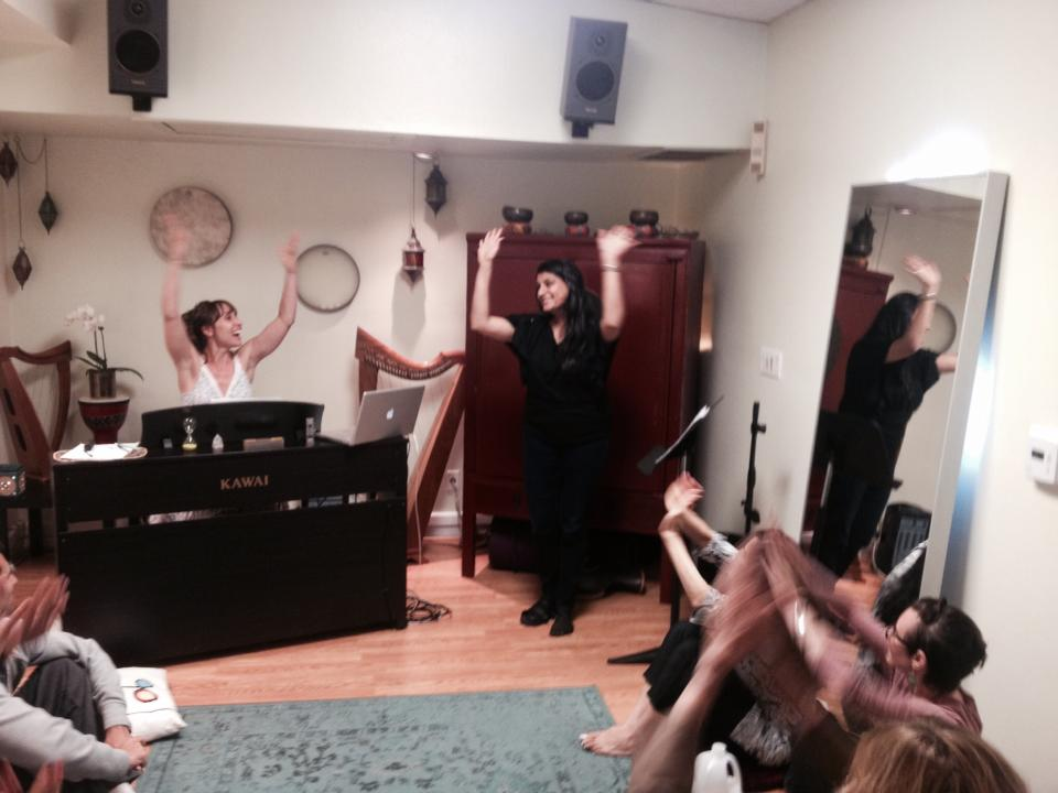 A voice class at the SFYS studio with everyone's happy hands in the air