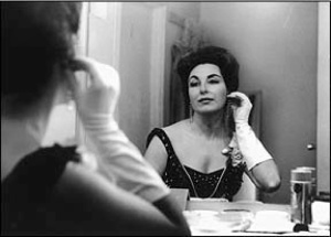 Phyllis Curtin, my former voice teacher, in a black and white style 1950's photo, looking in a mirror, wearing a black dress and white gloves, and putting an earring in. Classic beauty.
