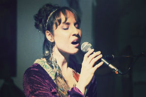 Headshot of our voice coach Kimberly singing at an event with a microphone, and wearing a purple dress
